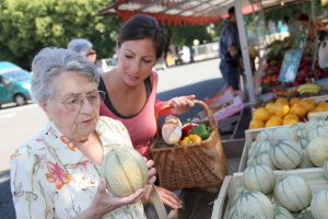 Caregiver assisting senior woman in buying foods